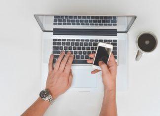 personne consultant son ordinateur, smartphone à la main