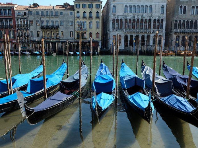 Des rangées de gondoles reposent dans l'eau claire des canaux de Venise.